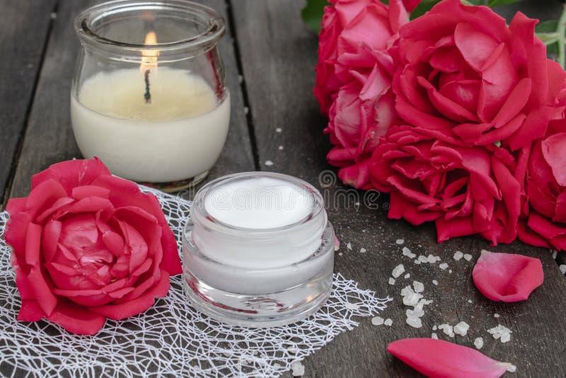 Kosmetische Creme und Rosen mit den Blumenblättern und einer brennenden Kerze auf dem alten hölzernen Hintergrund stockfotos