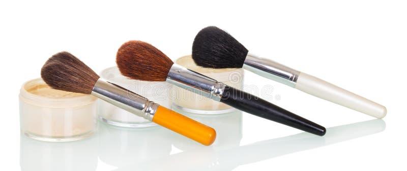 Kosmetische die borstels en kruikenroom, stichting op witte achtergrond wordt geïsoleerd stock afbeeldingen