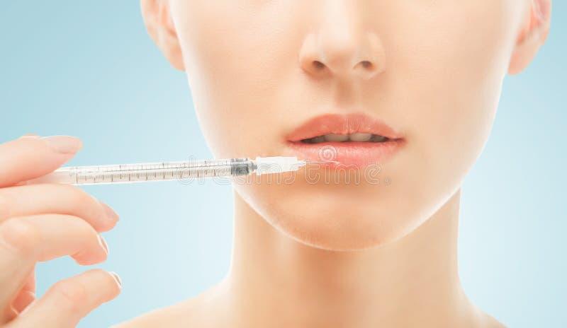 Kosmetische Einspritzung in der unteren Lippe der Frau lizenzfreie stockfotos