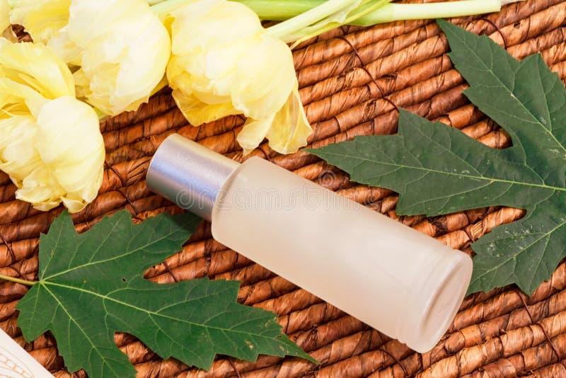 Kosmetische Flasche, gelbe Tulpen, Grünblätter und hölzerner Hintergrund lizenzfreie stockfotos