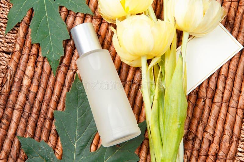 Kosmetische Flasche, gelbe Tulpen, Grünblätter und hölzerner Hintergrund stockbild