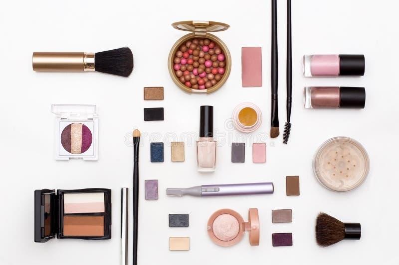 Kosmetische Make-upbürste, Gesichtspuder, Lidschatten, Nagellack, Trimmer und anderes Zubehör auf Draufsicht des weißen Hintergru lizenzfreie stockfotografie
