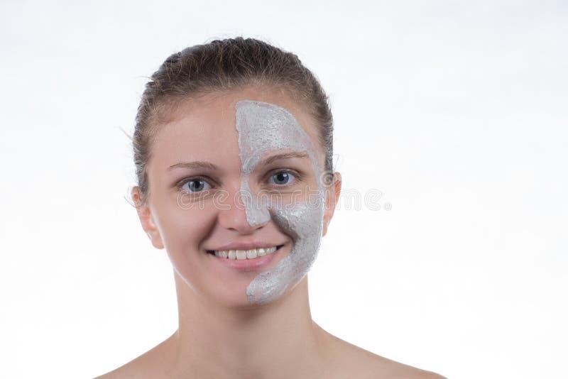 Kosmetische Maske des grauen Lehms mit scheuern sich auf dem Gesicht eines jungen gir lizenzfreie stockfotos