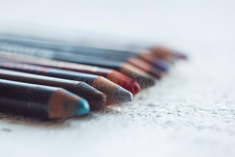 Kosmetische potloden voor het toepassen van make-up op het gezichtsclose-up oogvoering in macro op vage achtergrond stock foto