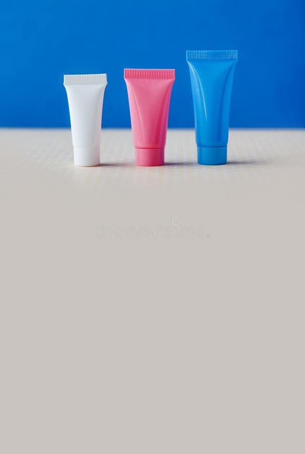 Kosmetische Rohre der Hygiene auf blauem und beige Hintergrund Drei leere Plastikbehälter, einfache Verpackungsgestaltung flach lizenzfreie stockfotos