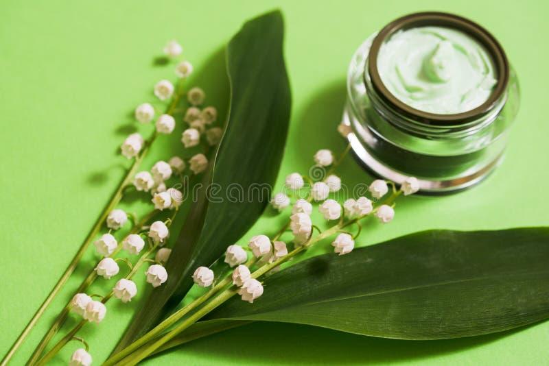 kosmetische room en lelietje-van-dalenbloemen op een groene achtergrond stock foto