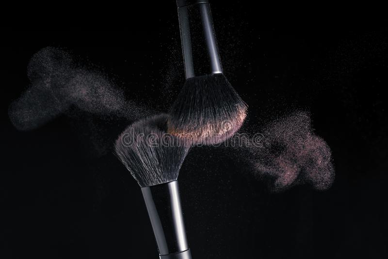 Kosmetische Schatten von verschiedenen Farbschatten, Streuung von zwei Make-upbürsten, die ein fantastisches Muster auf einem sc lizenzfreie stockfotos