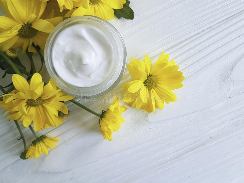 Kosmetische van de wellnessmargriet van de vochtinbrengende crèmeroom van het de chrysantenproduct gele de kamille witte houten stock afbeeldingen