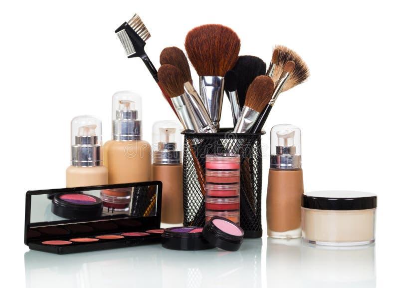 Kosmetische verfborstels, flessen met stichting, lipgloss, elft stock foto's