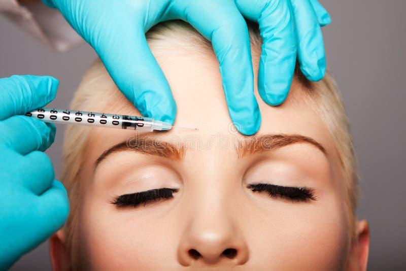 Kosmetischer plastischer Chirurg, der Ästhetikgesicht einspritzt stockfotografie