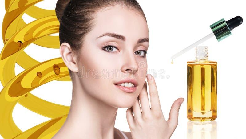 Kosmetisches Öl, das auf Gesicht der jungen Frau zutrifft lizenzfreie stockbilder