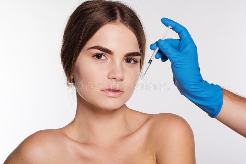 Kosmetisk antiwrinkleinjektion till flickas framsida royaltyfri bild