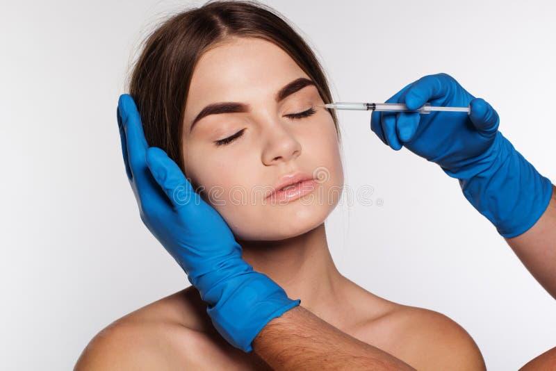 Kosmetisk antiwrinkleinjektion till kvinnas framsida royaltyfri fotografi