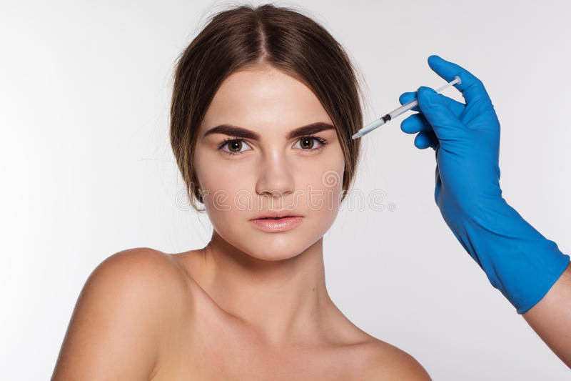 Kosmetisk antiwrinkleinjektion till kvinnas framsida royaltyfria bilder