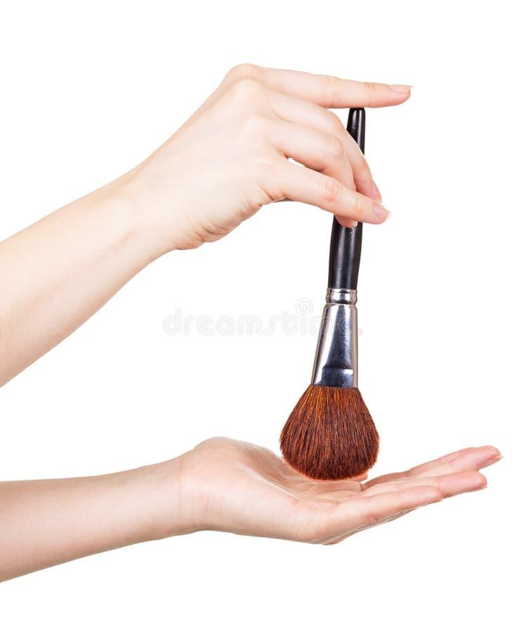 Kosmetisk borste för makeup i handkvinnor som isoleras på vit fotografering för bildbyråer
