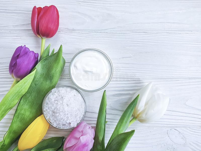 Kosmetisk fuktighetsbevarande hudkrämkräm, saltar, blomman för salvaskönhettulpan på en vit träbakgrund arkivbild