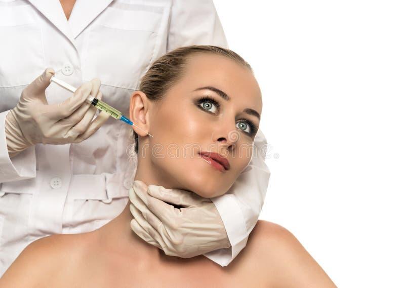 Kosmetisk injektion till de nätta härliga kvinnaframsida- och kosmetologhänderna med injektionssprutan. royaltyfria foton