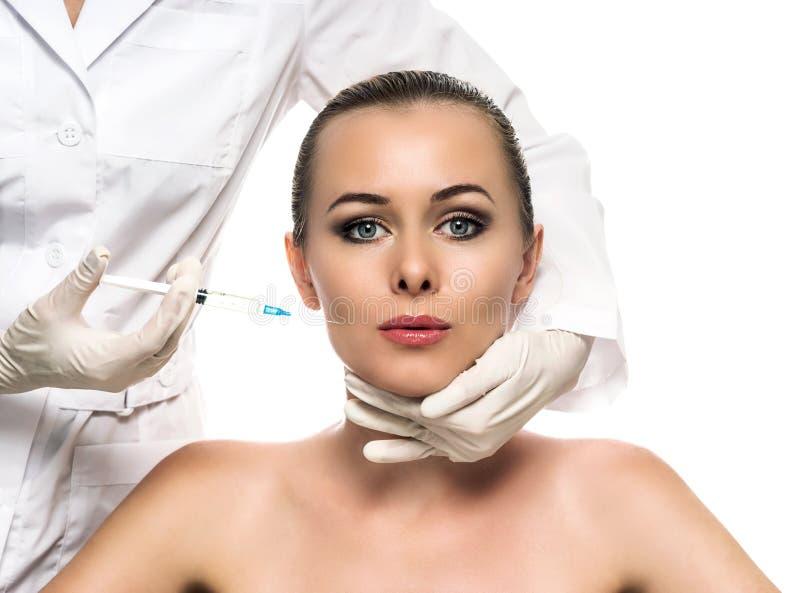 Kosmetisk injektion till de nätta härliga kvinnaframsida- och kosmetologhänderna med injektionssprutan. arkivfoto