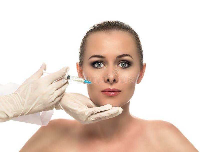 Kosmetisk injektion till de nätta härliga kvinnaframsida- och kosmetologhänderna med injektionssprutan. royaltyfri foto