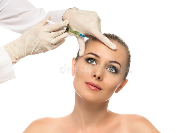 Kosmetisk injektion till de nätta härliga kvinnaframsida- och kosmetologhänderna med injektionssprutan. royaltyfri fotografi