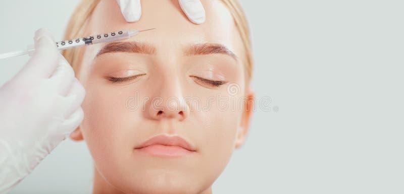 Kosmetisk injektion till en ung kvinna arkivfoto