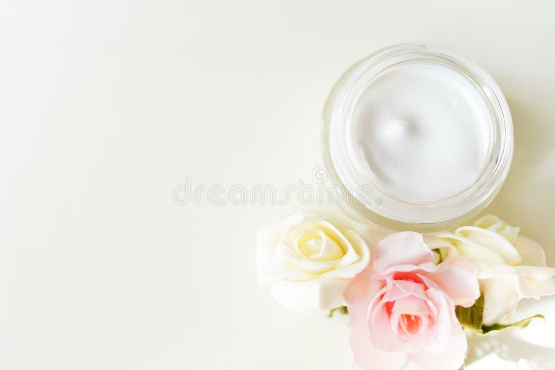 Kosmetisk kräm med växt- blommor på den vita tabellen med kopieringsutrymme Dekorativ etikett f?r design Begrepp f?r hudkroppomso arkivfoton