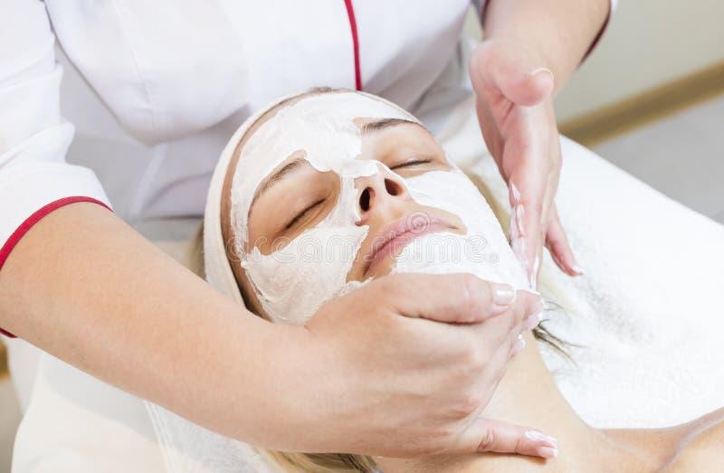 Kosmetisk maskering för process av massagen och ansiktsbehandlingar arkivbild