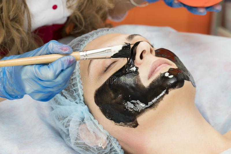 Kosmetisk maskering för process av massagen och ansiktsbehandlingar royaltyfri foto
