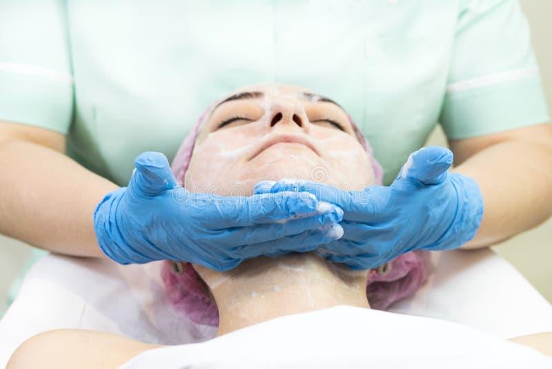 Kosmetisk maskering för process av massagen och ansiktsbehandlingar arkivfoton