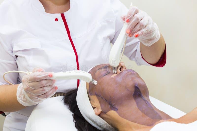 Kosmetisk maskering för process av massagen och ansiktsbehandlingar royaltyfria foton