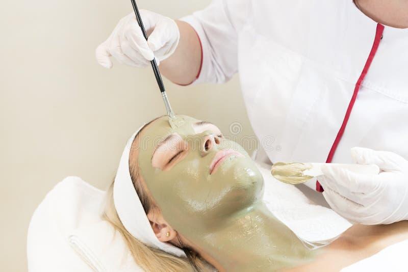 Kosmetisk maskering för process av massagen och ansiktsbehandlingar arkivbilder