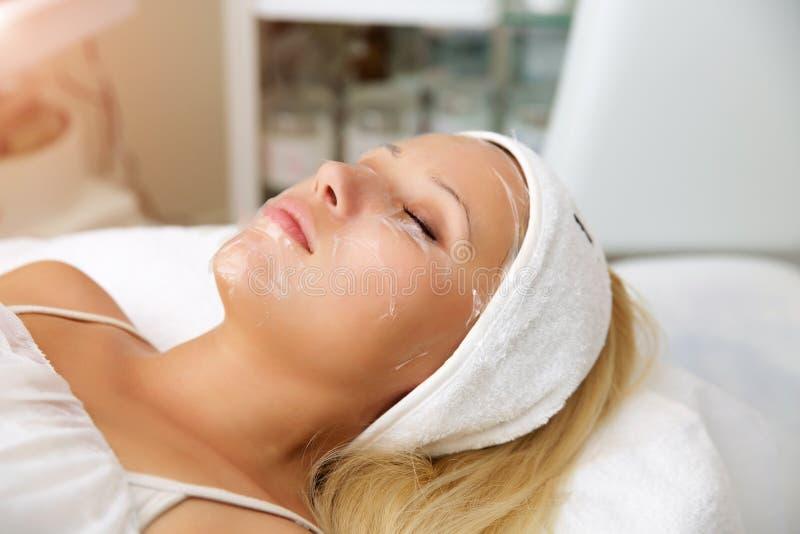 Kosmetisk maskering för process av massagen och ansiktsbehandlingar i skönhetsalong Cosmetologisten tar bort döda hudceller arkivfoto