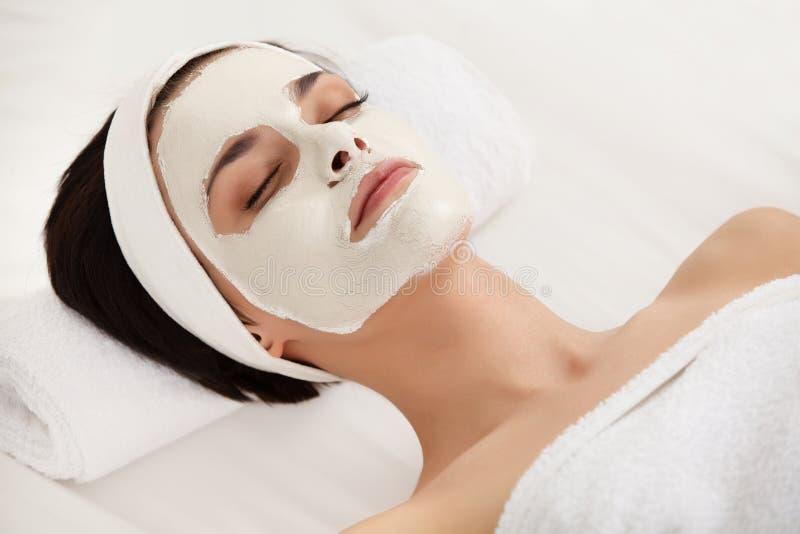 kosmetisk maskering Härlig ung kvinna som får en skönhetbehandling arkivfoton