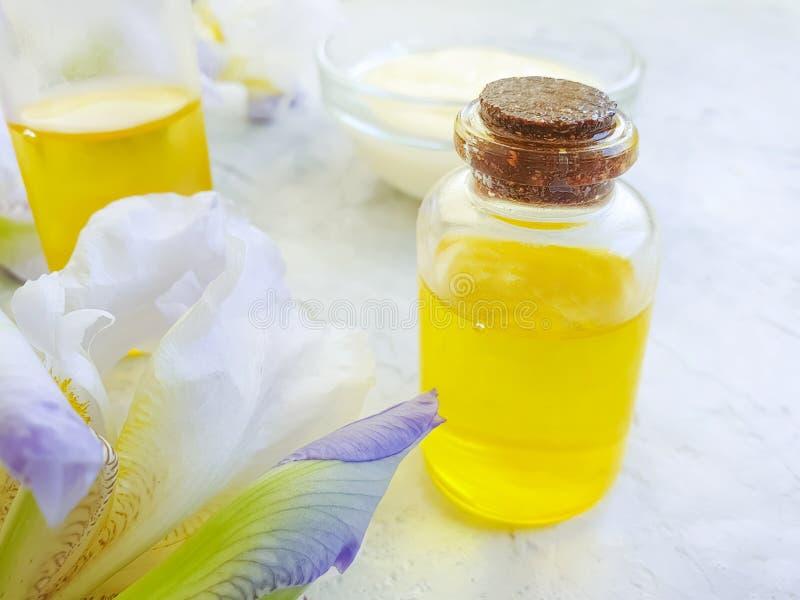 Kosmetisk olja, kräm, naturlig blommairisextrakt på en grå konkret bakgrund fotografering för bildbyråer