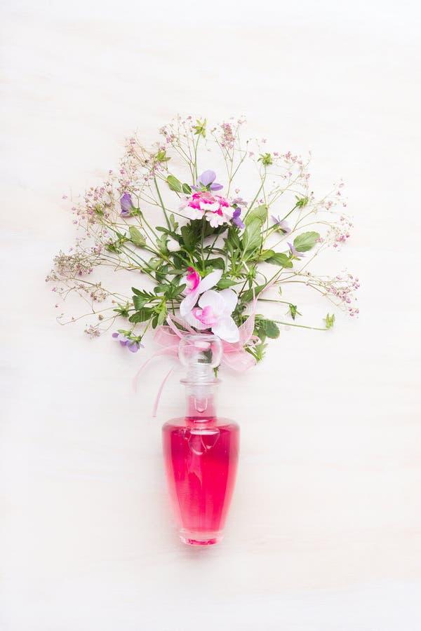 Kosmetisk produktglasflaska med rosa flytande och gruppen av blommor på vit träbakgrund royaltyfri bild
