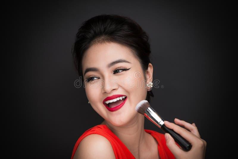 Kosmetisk pulverborste Asiatisk kvinna som applicerar rouge på hennes kind fotografering för bildbyråer