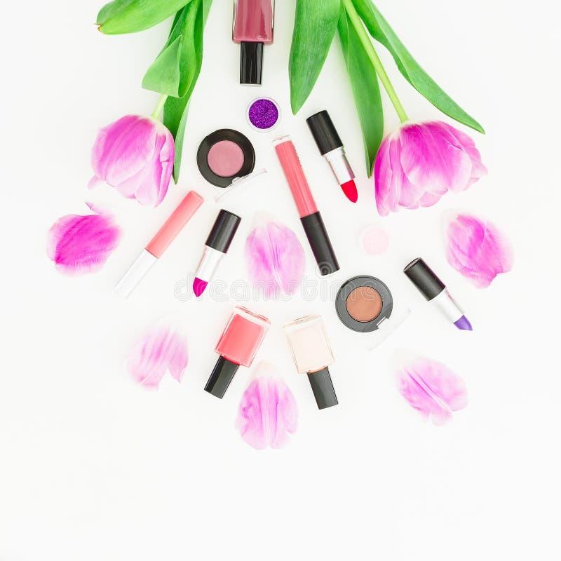 Kosmetisk sammansättning med den rosa tulpan blommar buketten och skönhetsmedel på vit bakgrund Top beskådar Lekmanna- lägenhet H arkivfoto