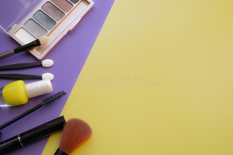kosmetisk tillbehör Borste för rodnad, borste, fernissa på en guling, purpurfärgad bakgrund royaltyfri fotografi