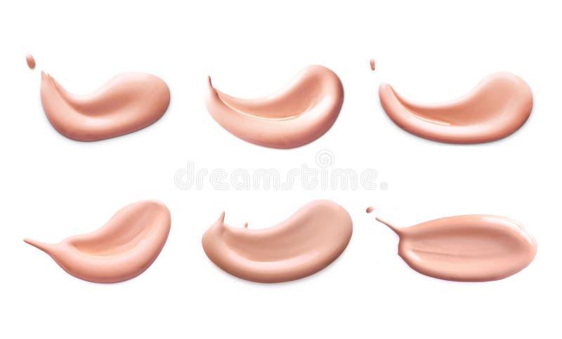 Kosmetisk vätskeuppsättning för slaglängder för underlagskrämfläcksudd Sminksudd som isoleras på vit bakgrund royaltyfria foton