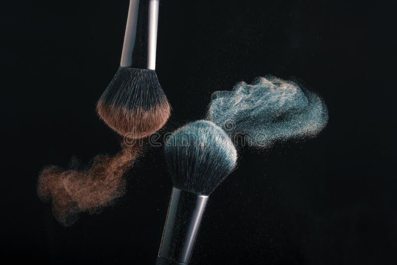 Kosmetiska skuggor av olika färger, rött och blått, fluga i väg från två sminkborstar som skapar en utsmyckad modell på en royaltyfri fotografi