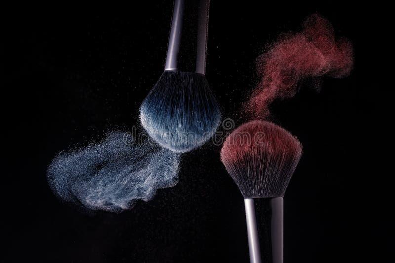 Kosmetiska skuggor av olika f?rger, r?tt och bl?tt, fluga i v?g fr?n tv? sminkborstar som skapar en utsmyckad modell p? en svart arkivfoto