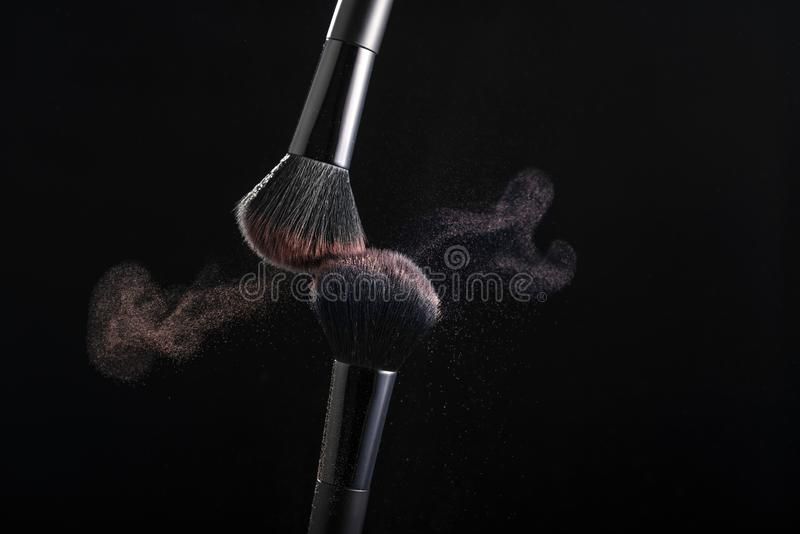 Kosmetiska skuggor av olika färgskuggor, sprider från två makeupborstar som skapar en utsmyckad modell på en svart bakgrund arkivbilder