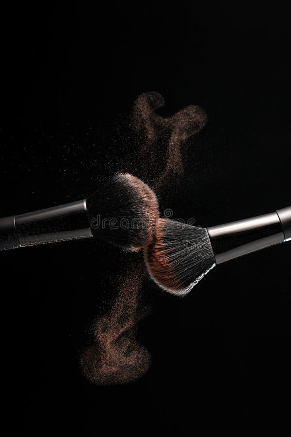 Kosmetiska skuggor av olika färgskuggor, sprider från två makeupborstar som skapar en utsmyckad modell på en svart bakgrund royaltyfri fotografi