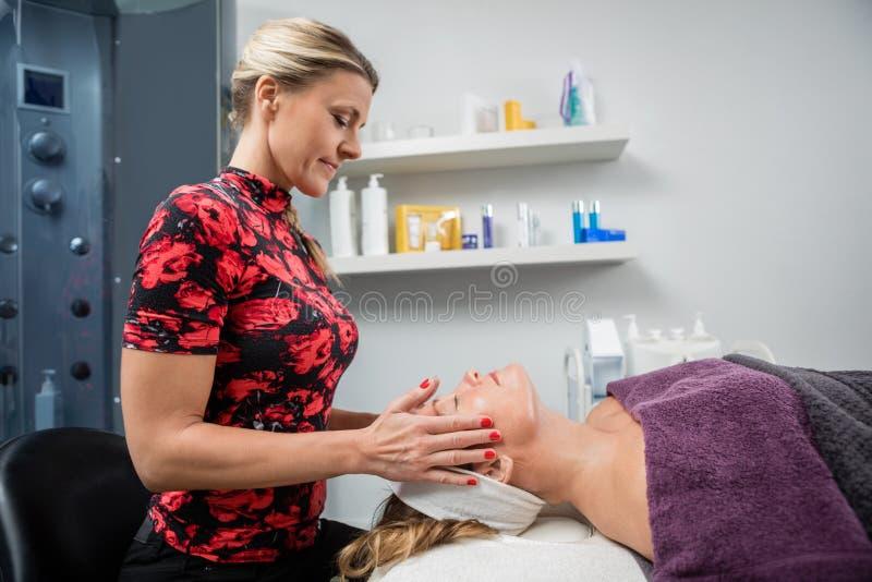 Kosmetolog Giving Facial Massage till kvinnan i skönhetmottagningsrum fotografering för bildbyråer