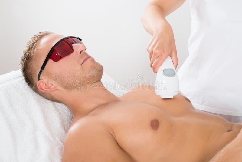 Kosmetolog Giving Laser Epilation på mans bröstkorg royaltyfri foto