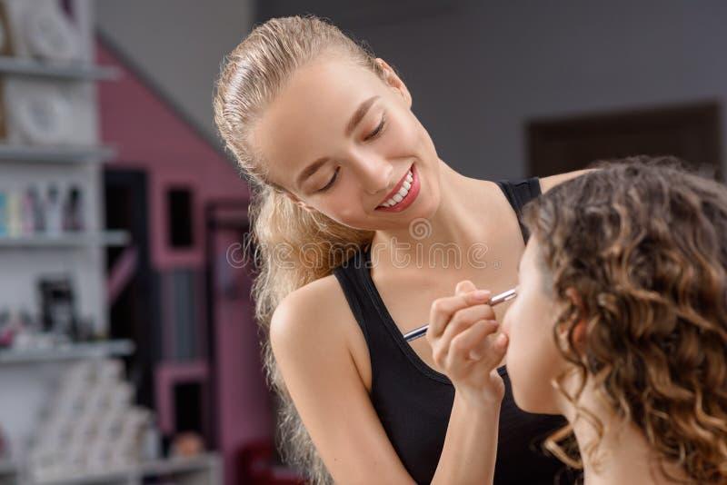 Kosmetolog i process av att göra makeup i skönhetsalong arkivfoton