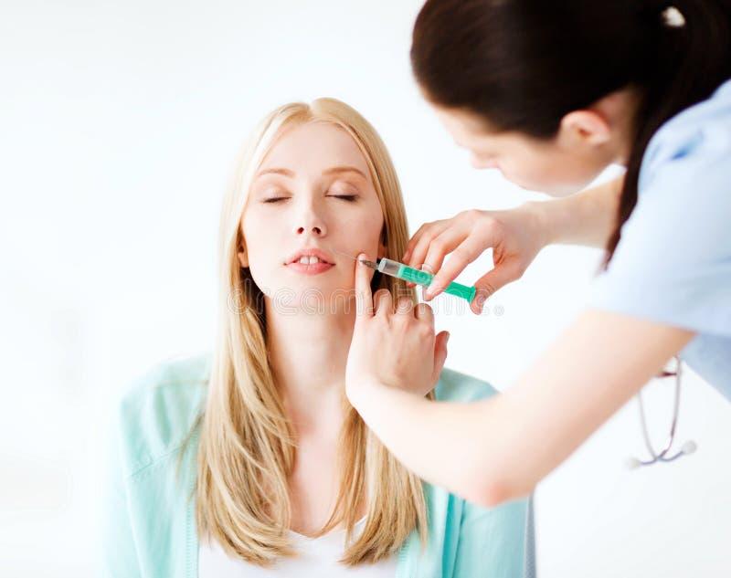 Kosmetolog med den tålmodiga görande botoxinjektionen royaltyfri bild