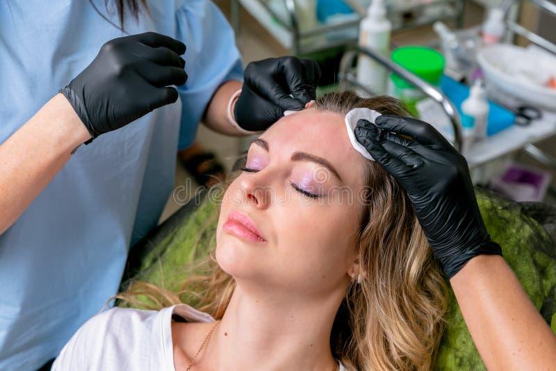 Kosmetolog med en assistentfest pannan av en kvinna efter en injektion Ung kvinna på cosmetological tillvägagångssätt N?rbild fotografering för bildbyråer