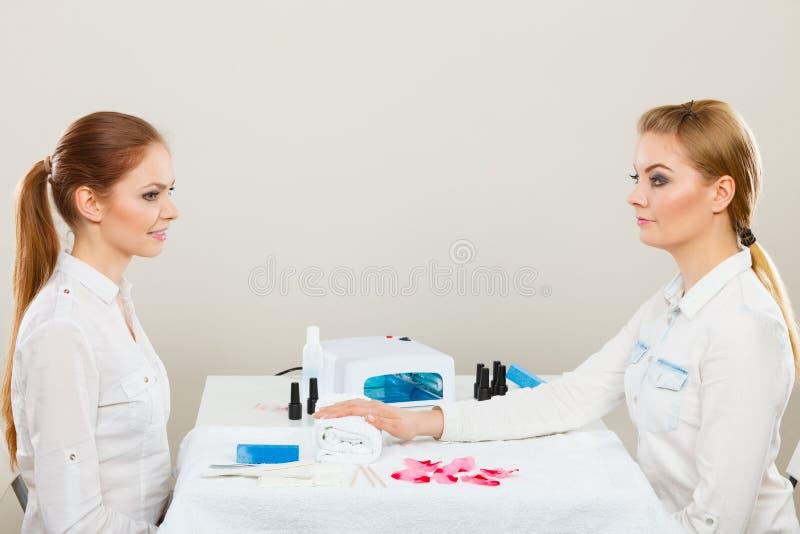 Kosmetolog med klienten på skönhetsalongen arkivfoto