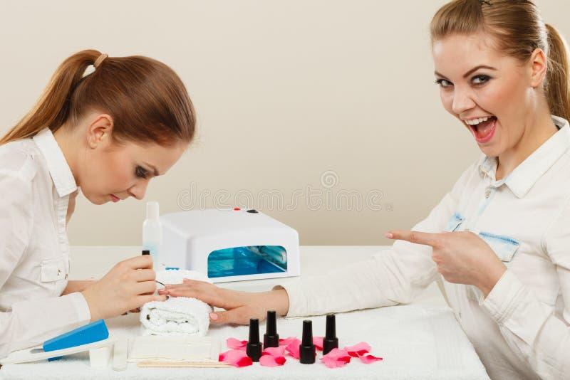 Kosmetolog med klienten på skönhetsalongen arkivbild